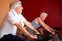 Two happy senior people on spinning bikes in gym