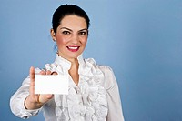 Beautiful businesswoman in white shirt holding a blank business card and standing in front of blue background