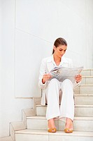 Business woman sitting on the stairs reading a newspaper