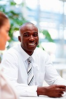 Happy young African American man at a business meeting