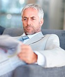 Portrait of an aged business man busy reading newspaper