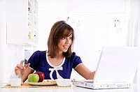 young woman in breakfast, eating and using laptop in amezement