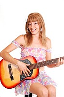 A beautiful woman sitting and playing the guitar in a light colorful short top and skirt, for white background.