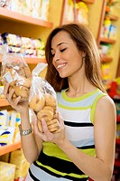 woman in a supermarket reading nutrition information and comparing two products