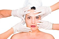 Hands with latex gloves touching a surprised woman face preparing her for surgical procedure with botox on white background,
