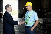 Manager shakes hands with one of his warehouse workers.