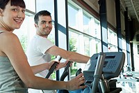 Man and woman use elliptical trainers for exercise at the gym.