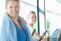 Two women smile while working out on elliptical machines.