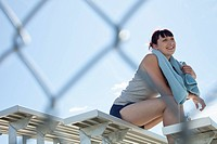 Young woman in active wear sitting on bleachers.