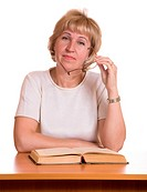 The mature woman with book behind a table on white background