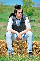 young attractive man posing on hay bale
