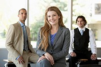 Businesswoman sits and smiles at the camera with her colleagues in the background.