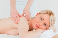 Closeup of young beautiful blonde female receiving a back massage in a spa centre