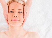 Happy blond_haired woman getting a massage on her face in a Spa centre