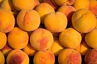 A background of tiled fresh yellow peaches.