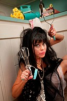 Drunk retro_styled woman with smeared mascara holding an egg beater and masher in kitchen
