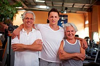 Fitness trainer and two seniors in a gym