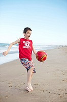 Boy playing football at the beach, El Saler beach, Albufera de Valencia Nature Reserve, Spain, Valencia