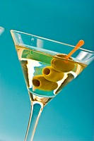one bocal of martini with olive over blue