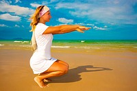 Young woman doing morning exercises close to the ocean
