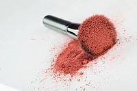 a flat blush brush with pink blush on it, placed on some loose powder blush, shot on white backgrownd.