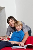 Portrait of a happy father helping son doing homework