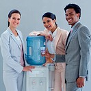 Smiling business people speaking next to a water cooler in office
