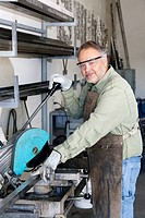 Portrait of a mature metalworker working with electric saw in workshop