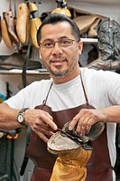 Portrait of a happy shoemaker cutting sole of footwear in workshop