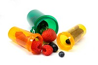 Assortment of berries spilling out of pill bottles as if the berries are medications photogrpahed on a white background