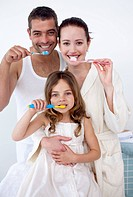 Happy parents and daughter cleaning their teeth together in bathroom