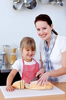 Smiling mother and daughter cutting bread in kitchen