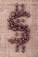 Dollar sign of dark roasted coffee beans on jute