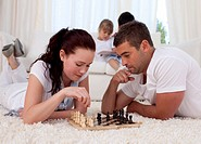 Parents playing chess on floor in living_room with their children on sofa