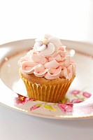 A cupcake topped with frosting and sugar flowers on a plate