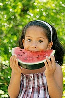 Latin little girl eating watermelon