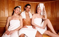 Man with two young women enjoying a sauna