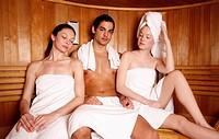 Man with two young women enjoying a sauna