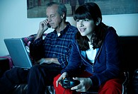 Grandfather works on laptop while granddaughter plays video game