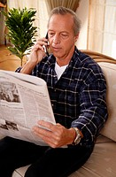 Mature man reading newspaper and talking on cell phone (thumbnail)