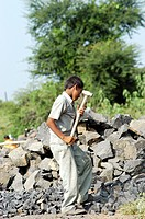 Indian Child Laborer Is Forced To Break Stones Used For The Construction Of Road Near A Village At Nanded, Maharashtra, India.