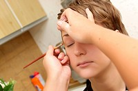 A cosmetologist applies eyeshadow for a girl