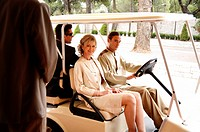 Couple being driven in cart by hotel bellboy
