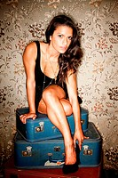 Woman sitting on vintage suitcases adjusting her high heel shoe