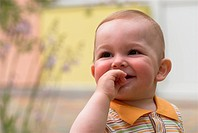 Cute little boy is looking up with fingers in his mouth
