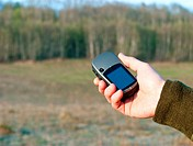Hand holding GPS navigator with spring field in background