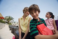 Boy with shopping bag, mother and sister in background