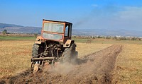Image of a field with a tractor ploughing.