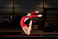 Gymnast jumping in air, bending backwards