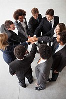 Business team members link hands in motivational exercise